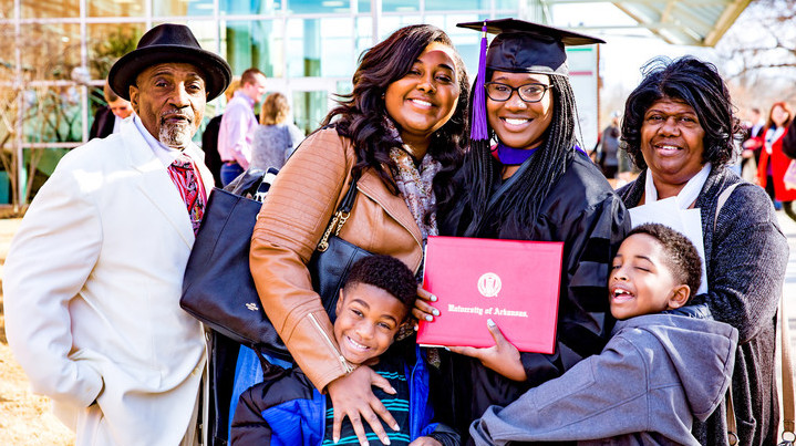 A graduate and her family celebrate after fall commencement